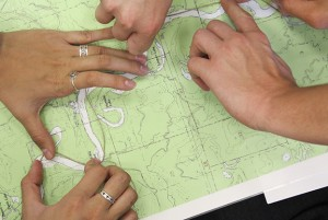 students' hands measuring distances on map