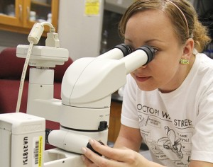 young woman using microscope