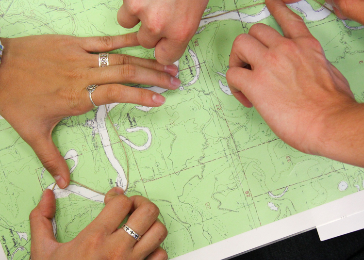 students' hands covering locations on a map