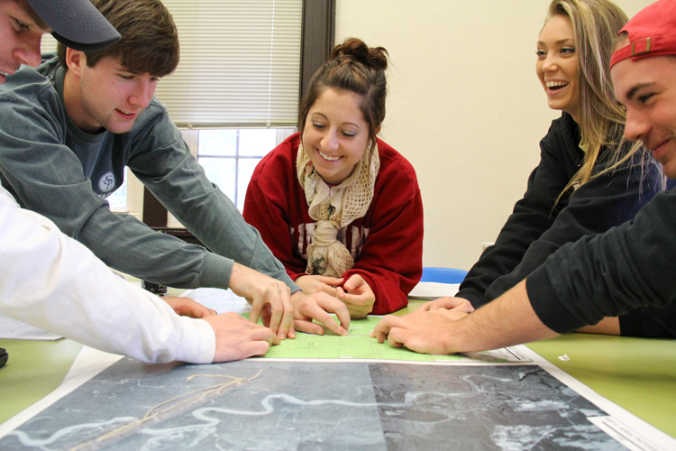 group of students identifying locations on a map